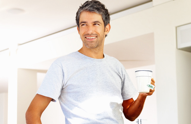 Mature man holding a cup of coffee in his kitchen