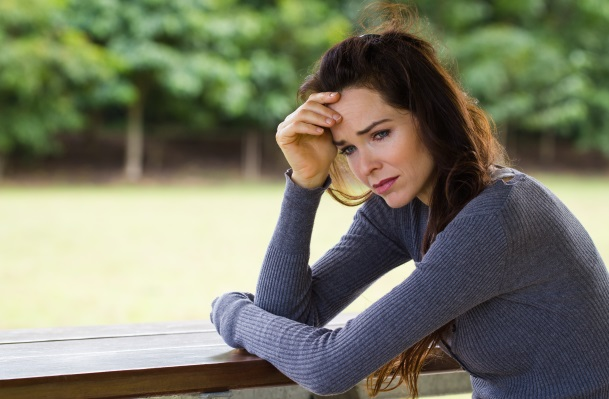 A sad and worried woman sitting down alone outdoors