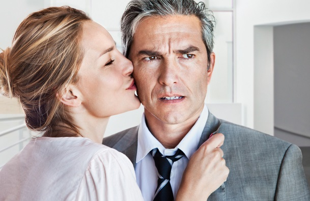 Woman kissing angry or concerned man on cheek